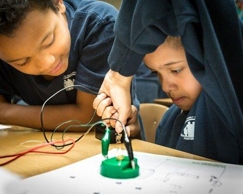 Two children having fun with a hands on STEM activity